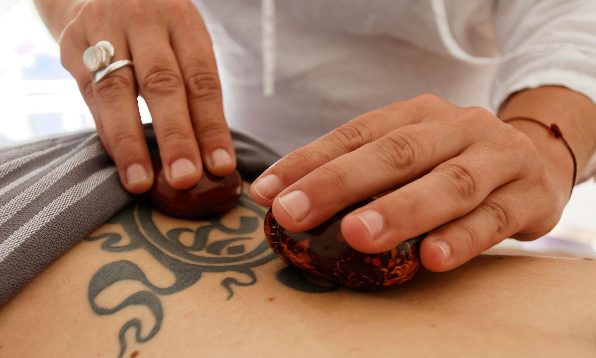 Mains applicant des pierres chaudes dans le dos